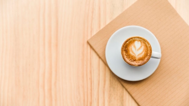 Overhead view of coffee latte and notebook on wooden backdrop