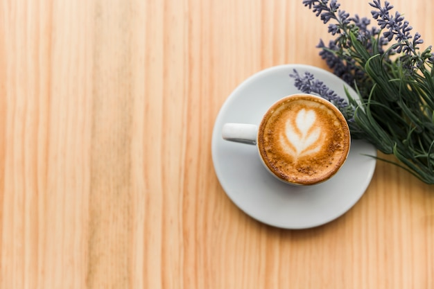 Overhead view of coffee latte with lavender flower on wooden table