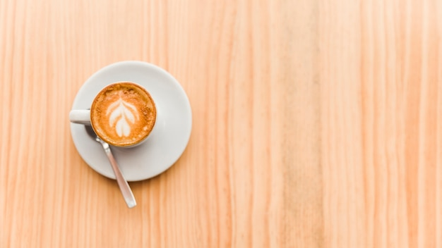 Overhead view of coffee latte on wooden background