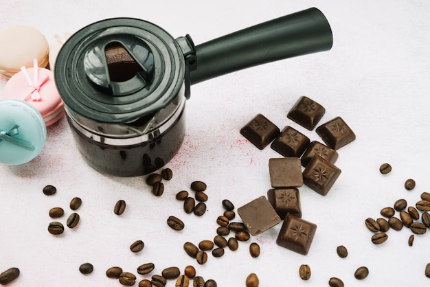 Overhead view of coffee maker with chocolate pieces and roasted coffee beans
