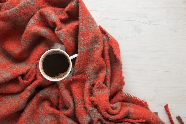 An overhead view of coffee on red blanket
