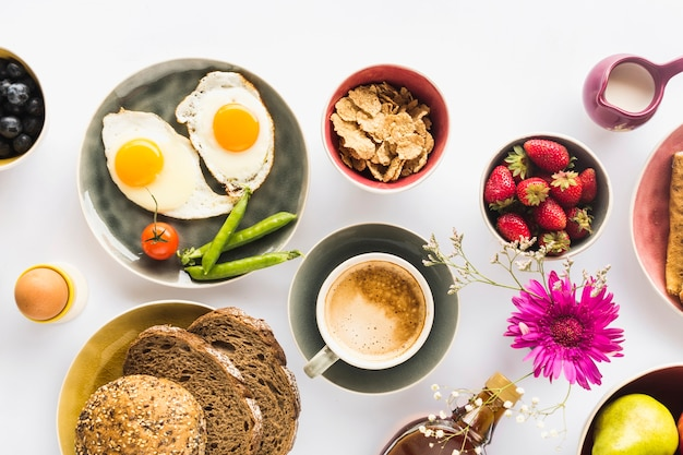 Overhead view of coffee with healthy snack on white background