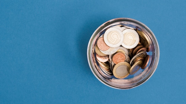An overhead view of coins in the glass jar on blue background