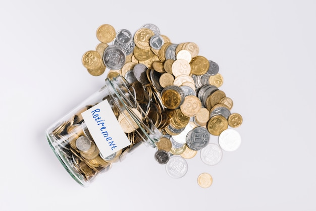 Overhead view of coins spilled out from retirement glass container on white background