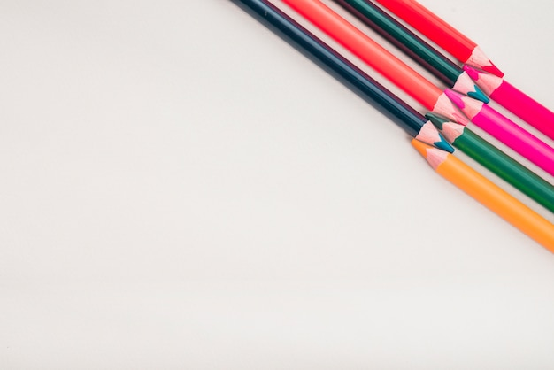 Overhead view of color pencils arranged at the corner of white background