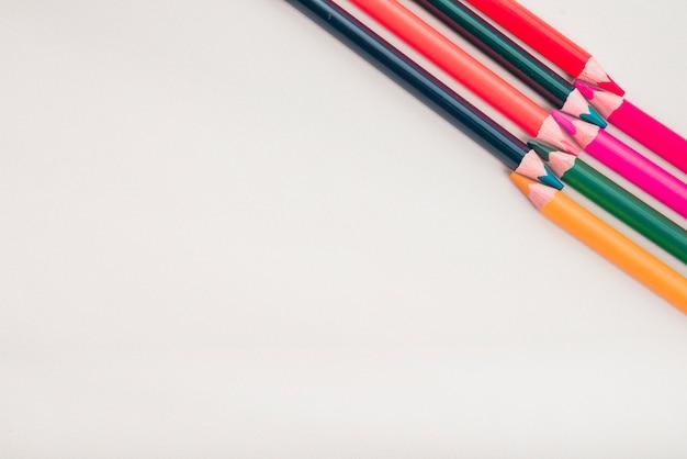 La vista sopraelevata delle matite di colore ha sistemato all'angolo di fondo bianco