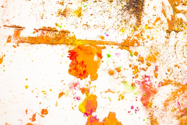 An overhead view of color powder mixed on white backdrop
