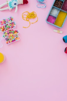 An overhead view of colorful beads in case on pink background