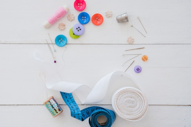 An overhead view of colorful buttons; thimble; needles; ribbon and measuring tape on white wooden desk
