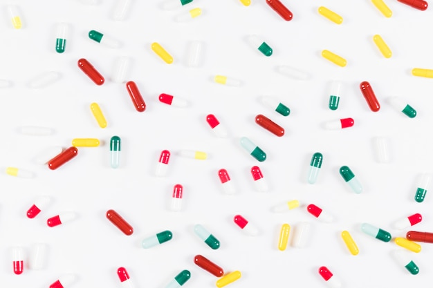 Overhead view of colorful capsules on white background