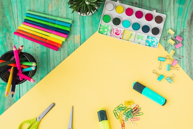 Overhead view of a colorful craft supplies and potted plant on wooden table