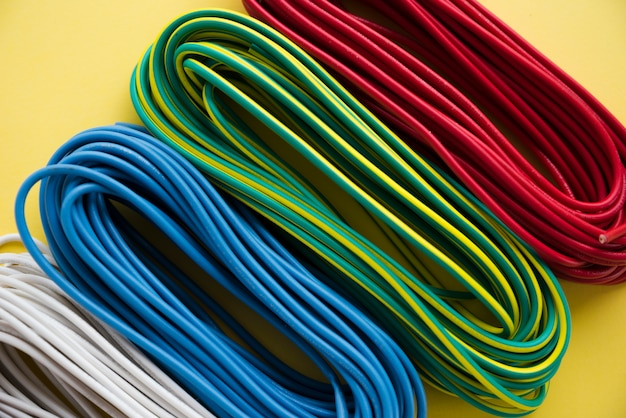 Overhead view of colorful electric wire bundle on yellow surface