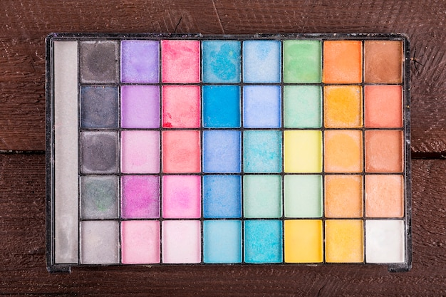 Overhead view of colorful eye shadow powder on wooden background