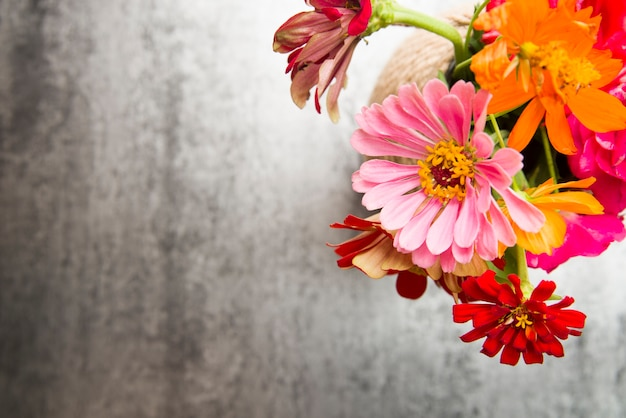 An overhead view of colorful flowers in the vase on textured backdrop