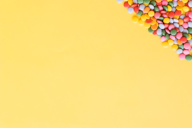 Overhead view of colorful gems candies on the corner of yellow background