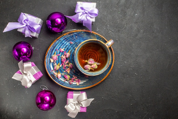 Overhead view of colorful gifts and decoration accessories a cup of black tea on dark background