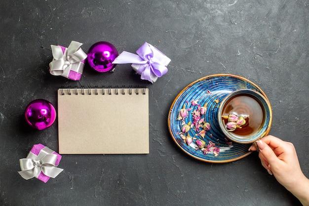 Vista dall'alto di regali colorati e accessori decorativi una tazza di tè nero accanto al taccuino su sfondo scuro