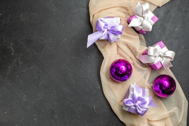 Vista dall'alto di regali colorati e accessori decorativi per il nuovo anno su un asciugamano di colore nudo su sfondo nero