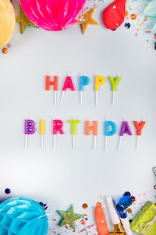 An overhead view of colorful happy birthday candles with party items on white backdrop