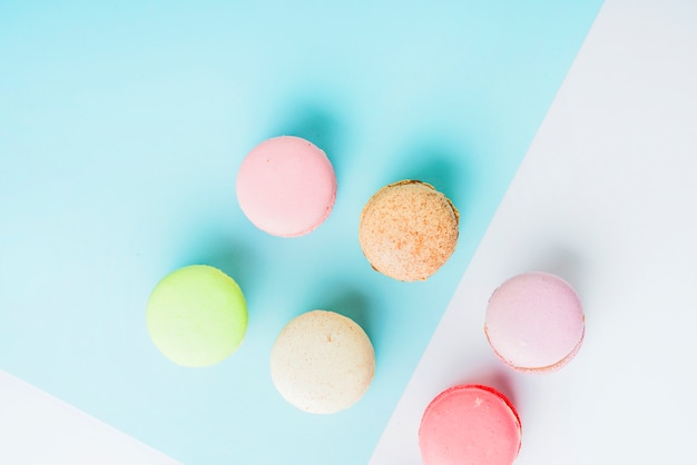 An overhead view of colorful macaroons on blue and white dual background
