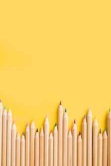 Overhead view of colorful pencils on yellow backdrop