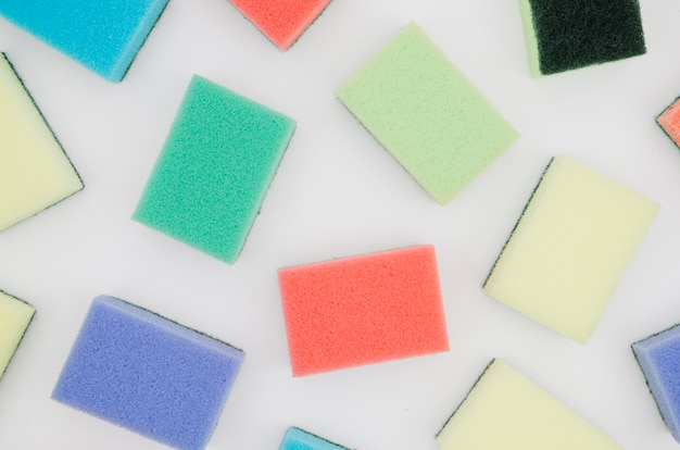 An overhead view of colorful sponges isolated on white backdrop