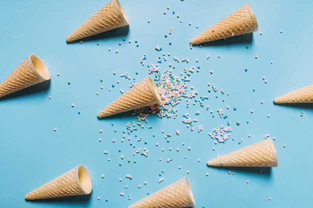 Overhead view of colorful sprinkles with waffle cones arranged on blue background