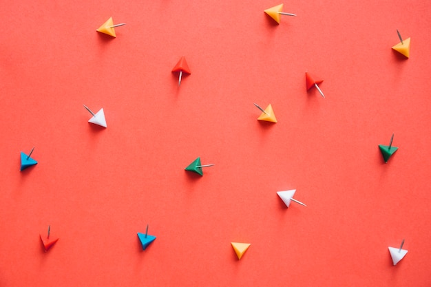 Overhead view of colorful triangular shaped push pins on orange background