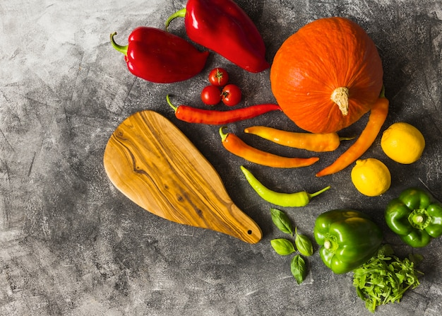 An overhead view of colorful vegetables and chopping board on grunge texture backdrop