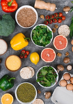 An overhead view of colorful vegetables and fruits on concrete background