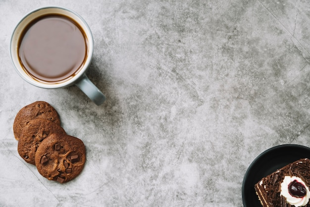 An overhead view of cookies; cake and coffee cup on an old backdrop