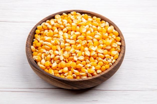 Vista dall'alto dei chicchi di mais in una ciotola marrone su sfondo bianco