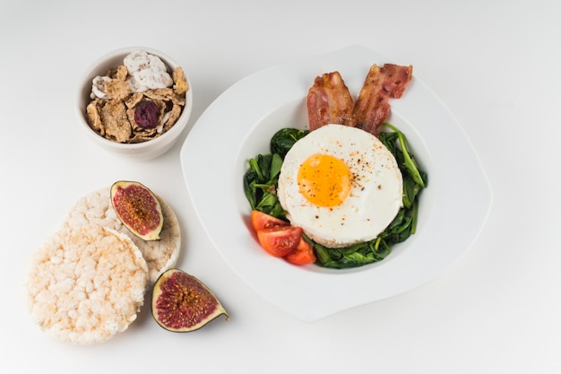An overhead view of cornflakes; rice cracker; fig and fried egg dish isolated on white background