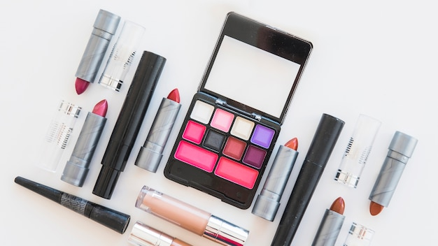 An overhead view of cosmetic eye shadows; different shades of lipstick; and brush on white background
