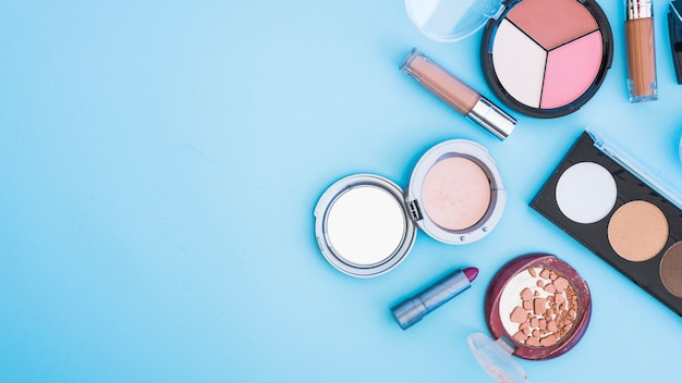 An overhead view of cosmetic face powder; lipstick; and foundation on blue backdrop