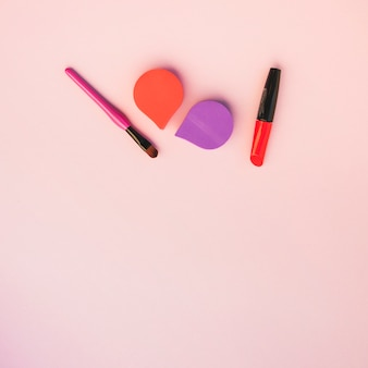An overhead view of cosmetic products over colored background