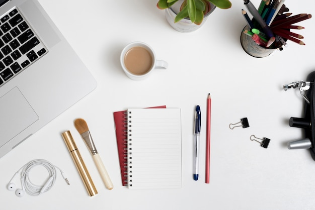 Overhead view of cosmetic products; office stationery; laptop and coffee cup with plant on office desk