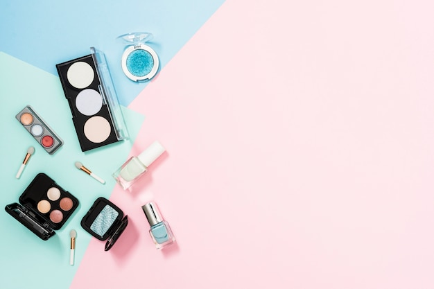 An overhead view of cosmetic products over the pastel background