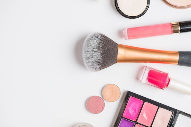 Overhead view of cosmetic products on white backdrop