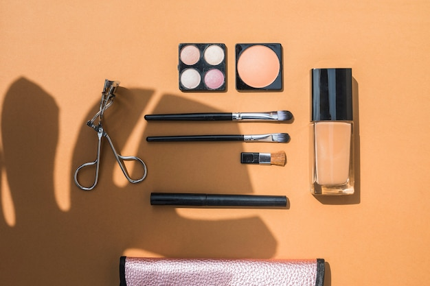 Overhead view of cosmetic products with brushes on orange backdrop