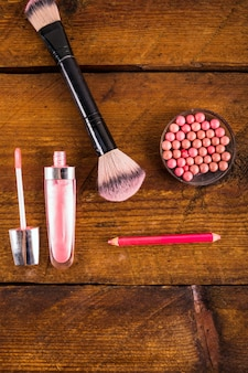 Overhead view of cosmetic products on wooden background