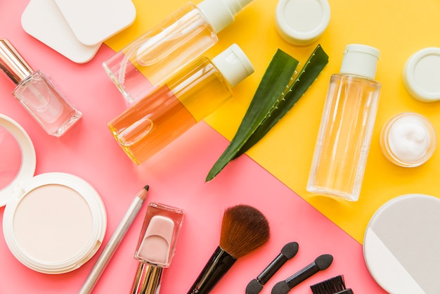An overhead view of cosmetics makeup and natural organic products on dual backdrop