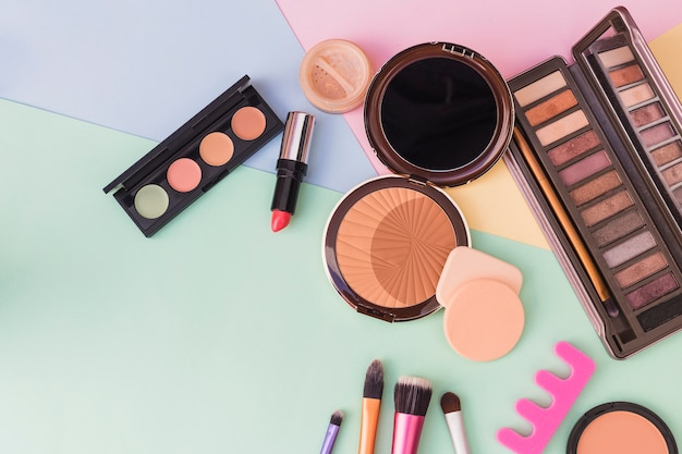 An overhead view of cosmetics products on colored background