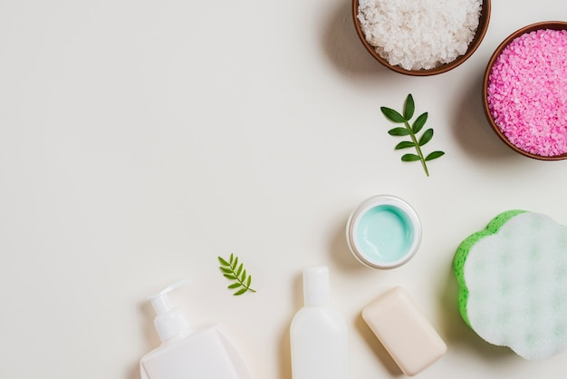 An overhead view of cosmetics products with salt bowls on white backdrop