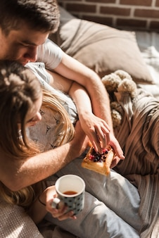 An overhead view of couple lying on bed holding pastry with berries and coffee cup