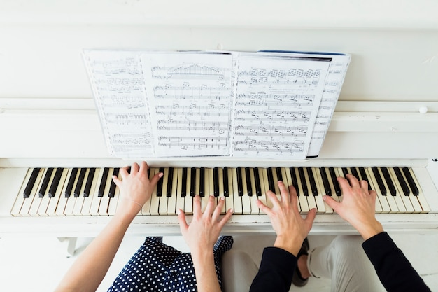 An overhead view of couple's hand playing piano with musical sheet