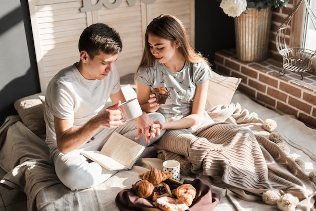 An overhead view of couple sitting on bed holding coffee cup and muffin in hand