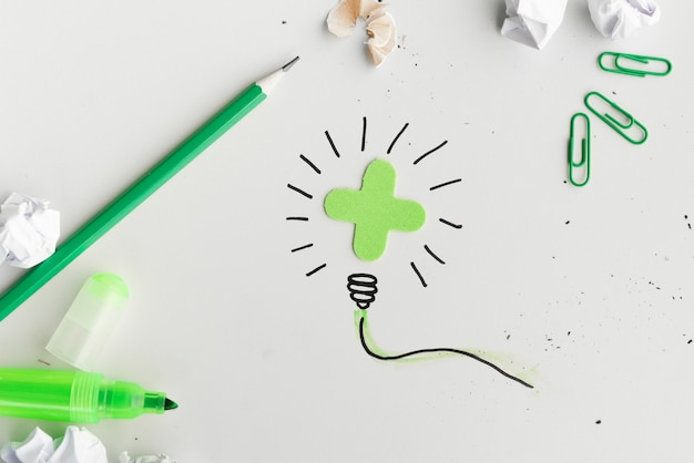 Overhead view of creative hand drawn light bulb with stationery product on white surface