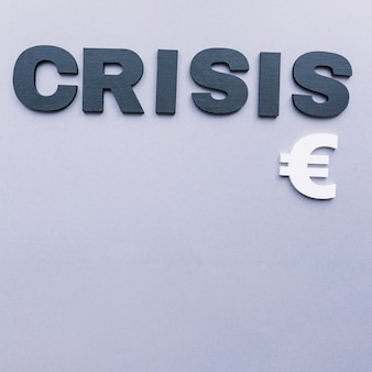 Overhead view of crisis word with euro sign on grey background