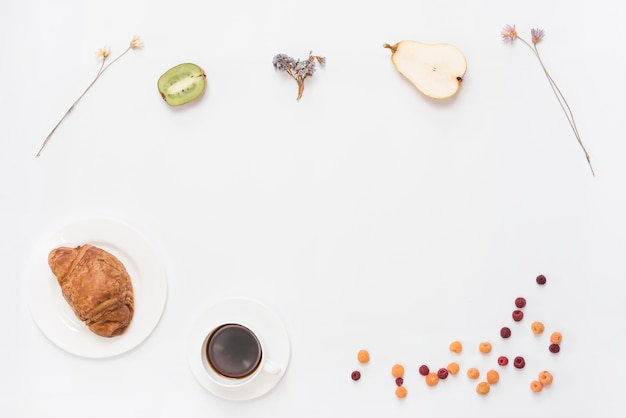 An overhead view of croissant coffee halved kiwi; pears; dried flower and raspberries on white background